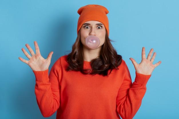Mulher jovem com aparência agradável mascando chiclete e soprando bolha no cabelo isolada em azul, parece assustada, estando em estado de choque, tem cara de surpresa