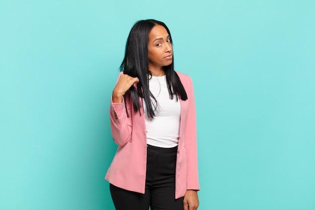 Mulher jovem com aparência arrogante, bem-sucedida, positiva e orgulhosa, apontando para si mesma