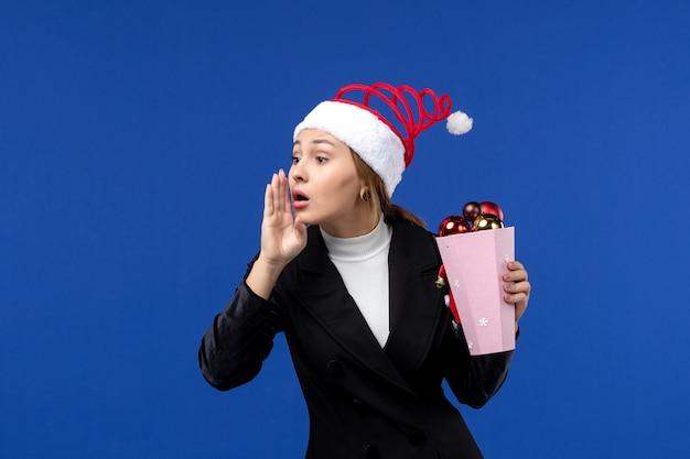 Mulher jovem com árvore de brinquedos na parede azul, cor de emoção de feriados de ano novo, de frente