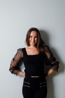 Mulher jovem com as mãos atrás da cintura e sorrindo graciosamente em blusa preta e calça preta e parecendo encantadora