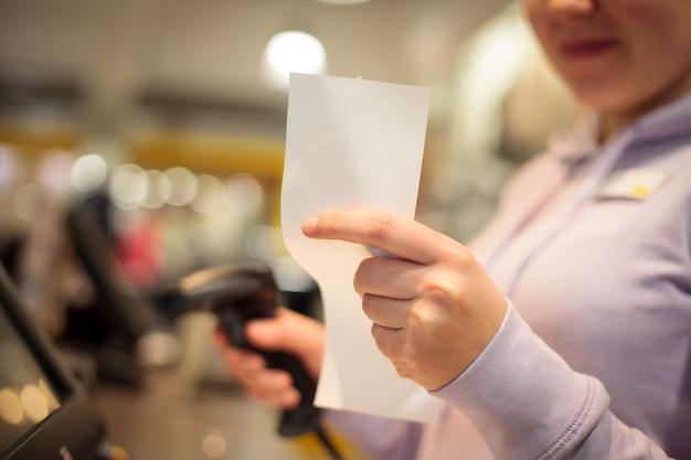 Mulher jovem com as mãos esperando a impressão da fatura de um cliente em um enorme shopping center