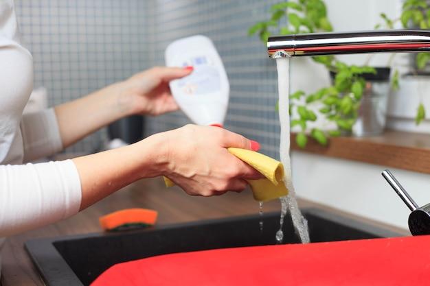 Mulher jovem com as mãos limpando alguns equipamentos de cozinha na pia
