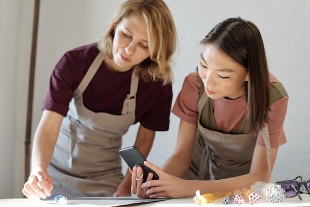 Mulher jovem com avental curvando-se sobre a mesa e colocando contas de vidro enquanto menina asiática morena com smartphone tirando foto da coleção