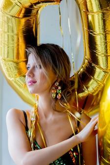 Mulher jovem, com, balões dourados, perto, janela