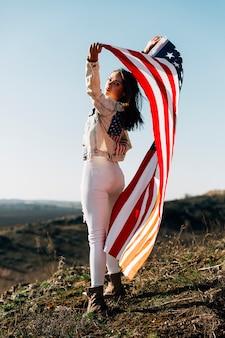 Mulher jovem, com, bandeira, ficar, sensually, em, luz solar