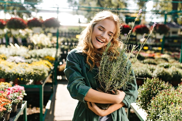 Mulher jovem com belos cabelos loiros e sorriso gentil, vestida com um manto verde com cinto está trabalhando em estufa
