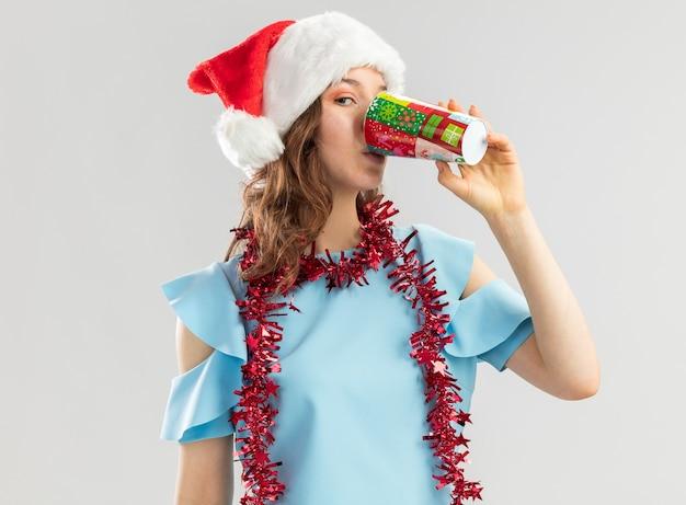 Mulher jovem com blusa azul e chapéu de papai noel com enfeites no pescoço bebendo de um copo de papel colorido feliz e positiva