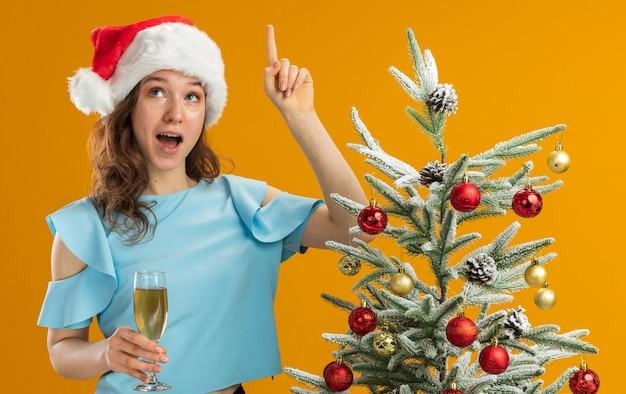Mulher jovem com blusa azul e chapéu de papai noel segurando uma taça de champanhe, olhando para cima surpresa, mostrando o dedo indicador tendo uma nova ideia ao lado de uma árvore de natal sobre uma parede laranja