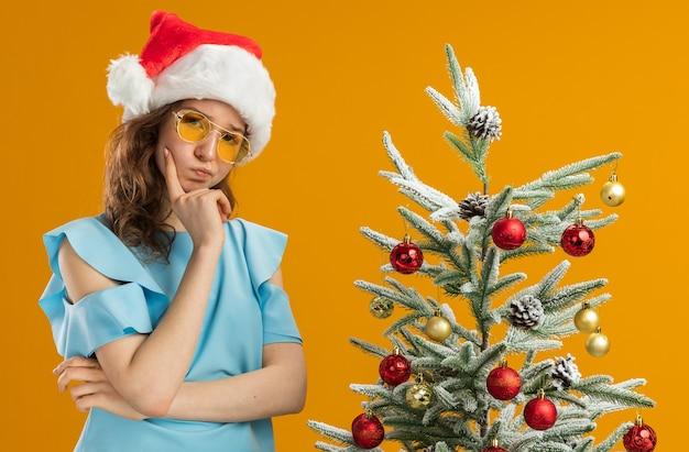 Mulher jovem com blusa azul e chapéu de papai noel usando óculos amarelos com a mão no queixo e pensando em pé ao lado de uma árvore de natal na parede laranja