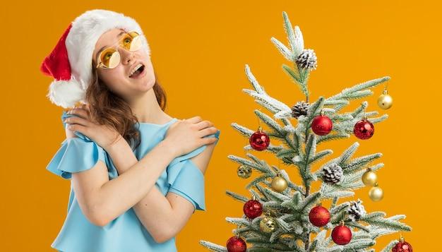 Mulher jovem com blusa azul e chapéu de papai noel usando óculos amarelos de mãos dadas no peito, feliz e positiva, sentindo-se grata em pé ao lado de uma árvore de natal sobre um muro laranja