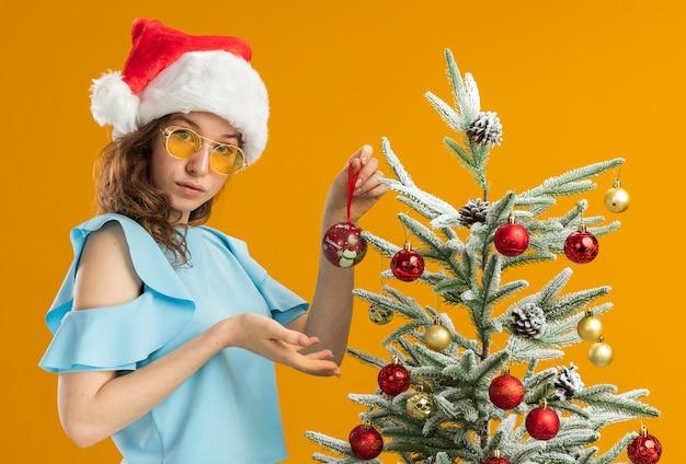Mulher jovem com blusa azul e chapéu de papai noel usando óculos amarelos, em pé ao lado de uma árvore de natal, segurando uma bola de natal, apresentando-a com o braço parecendo confiante sobre a parede laranja
