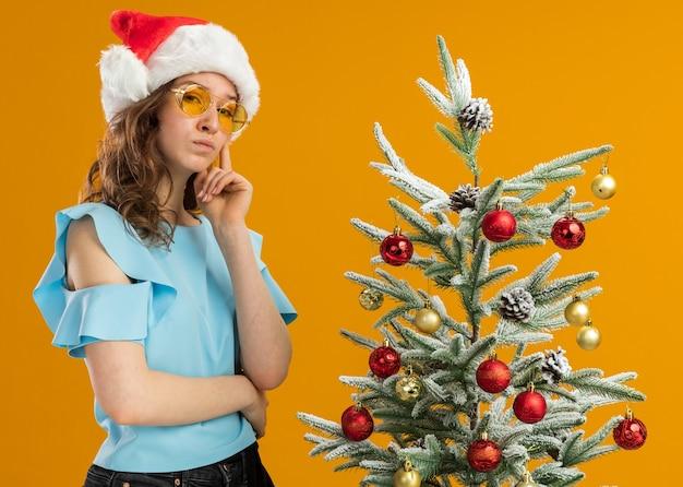 Mulher jovem com blusa azul e chapéu de papai noel usando óculos amarelos olhando com expressão pensativa e pensando em pé ao lado de uma árvore de natal sobre uma parede laranja