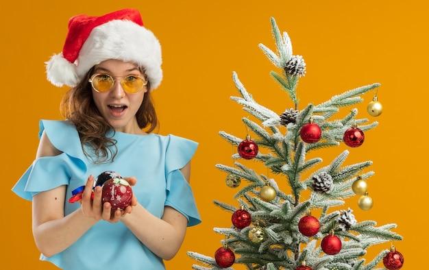 Mulher jovem com blusa azul e chapéu de papai noel usando óculos amarelos segurando bolas de natal, feliz e alegre, em pé ao lado de uma árvore de natal sobre uma parede laranja