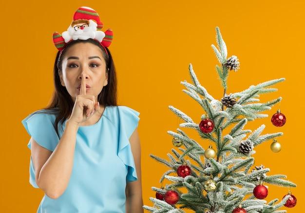 Mulher jovem com blusa azul, usando um aro de natal engraçado na cabeça, fazendo um gesto de silêncio com o dedo nos lábios, ao lado de uma árvore de natal sobre uma parede laranja