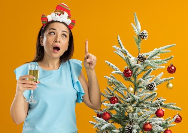 Mulher jovem com blusa azul, usando um aro de natal engraçado na cabeça, segurando uma taça de champanhe apontando para cima e sendo surpreendida, em pé ao lado de uma árvore de natal sobre uma parede laranja