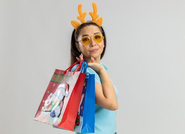 Mulher jovem com blusa azul, usando um aro engraçado com chifres de veado e óculos amarelos, segurando sacolas de papel com presentes de natal e sorrindo confiante