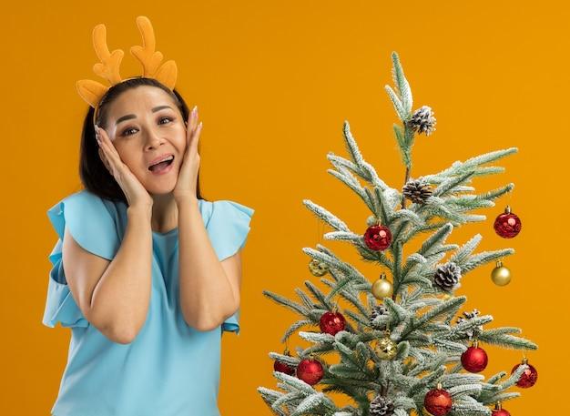 Mulher jovem com blusa azul, usando um aro engraçado com chifres de veado, surpresa e feliz em pé ao lado de uma árvore de natal sobre uma parede laranja
