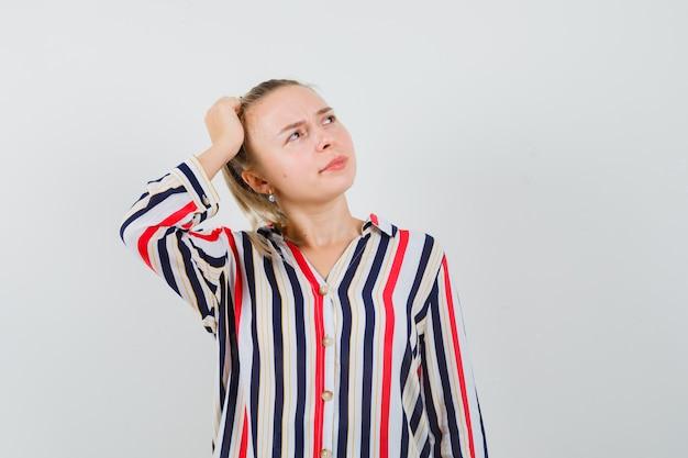 Mulher jovem com blusa listrada bota a cabeça na cabeça e parece indecisa