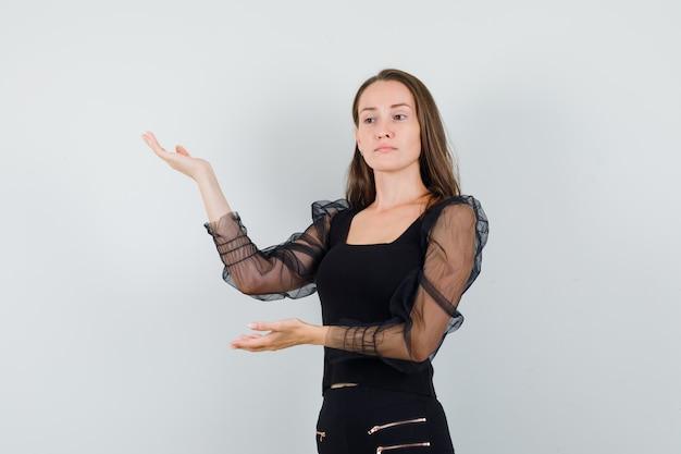 Mulher jovem com blusa preta levantando as mãos com as palmas abertas de lado e olhando focado