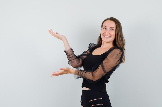 Mulher jovem com blusa preta levantando as mãos com as palmas abertas de lado e parecendo alegre