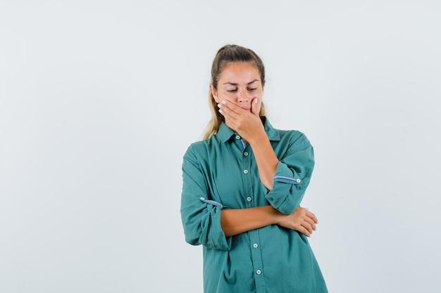 Mulher jovem com blusa verde bocejando e parecendo com sono