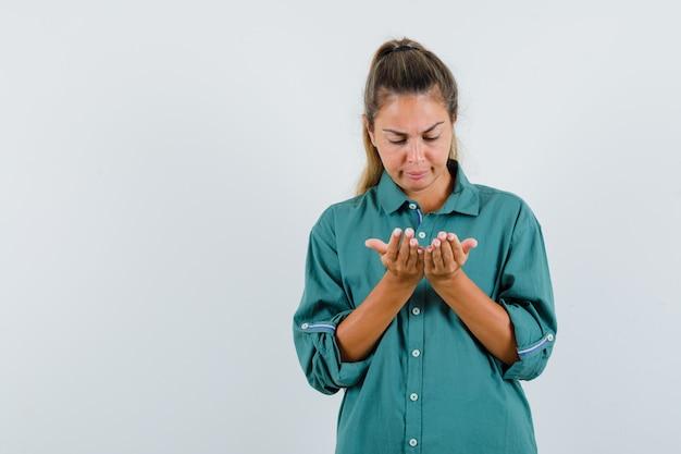Mulher jovem com blusa verde esticando as mãos e segurando algo imaginário, olhando para ele e olhando com foco