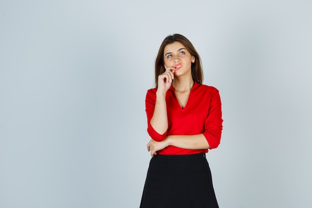 Mulher jovem com blusa vermelha e saia preta em pose pensativa