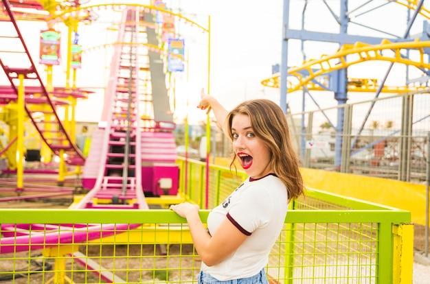 Mulher jovem, com, boca aberta, apontar, dela, dedo, em, montanha-russa, passeio