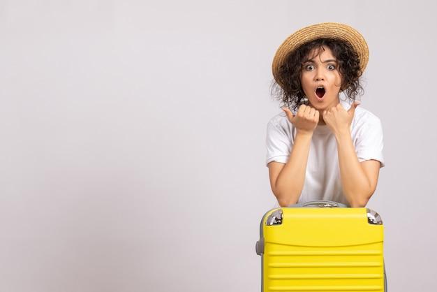 Mulher jovem com bolsa amarela se preparando para uma viagem no fundo branco voo resto viagem turista férias cor sol avião