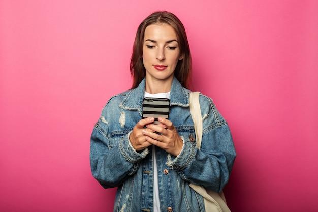 Mulher jovem com bolsa ecológica olhando para o telefone com foco na superfície rosa