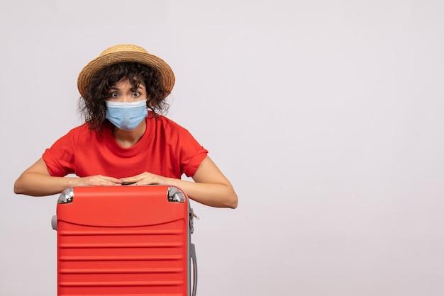 Mulher jovem com bolsa na máscara na cor de fundo branco covida- pandemia de vírus solar viagem turística