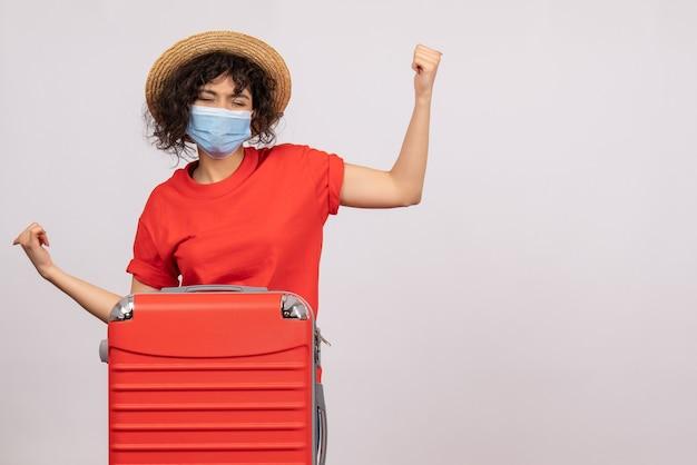 Mulher jovem com bolsa na máscara no fundo branco cor covid- férias pandêmicas de vírus solar viagem turistas