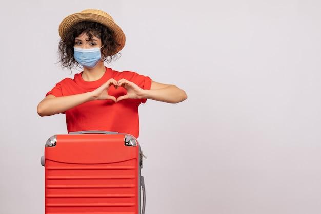 Mulher jovem com bolsa na máscara no fundo branco cor covid- férias sol vírus viagem turista
