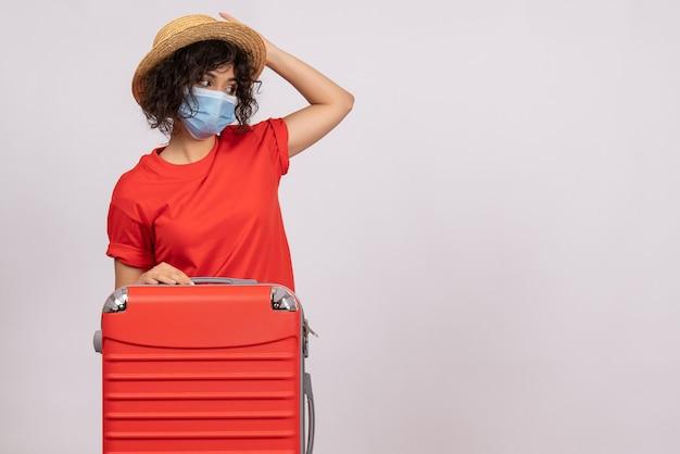 Mulher jovem com bolsa na máscara no fundo branco cor covid- voyage turista férias pandemia de sol vírus viagem