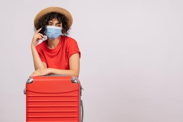 Mulher jovem com bolsa na máscara no fundo branco cor covid- voyage turista pandemia de sol vírus viagem