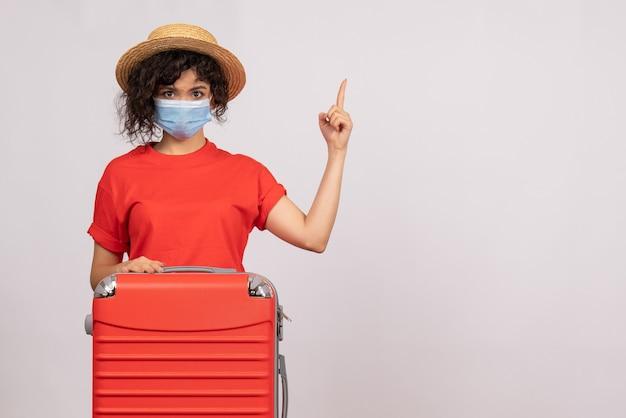 Mulher jovem com bolsa na máscara no fundo branco cor vírus covid- vista frontal