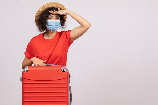 Mulher jovem com bolsa na máscara olhando para a distância no fundo branco cor covid- voyage turista férias pandemia de sol vírus viagem