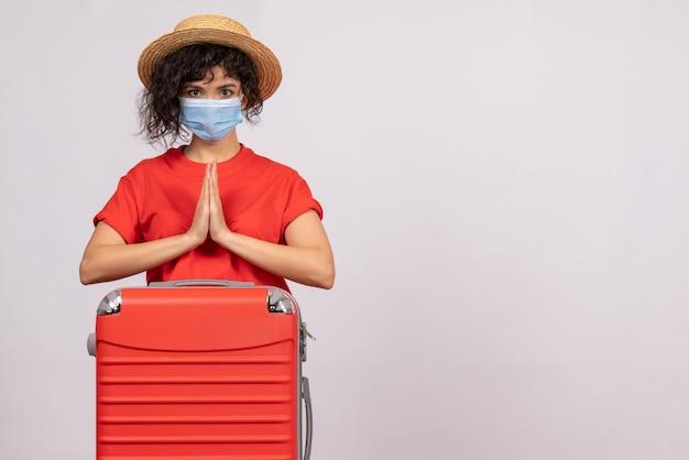 Mulher jovem com bolsa na máscara sobre fundo branco covida- pandemia de vírus solar viagem turística cor de férias