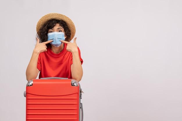 Mulher jovem com bolsa na máscara sobre um fundo branco cor do sol covidêmico - pandemia de férias, viagem turística