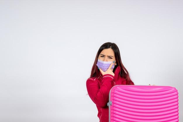Mulher jovem com bolsa rosa na máscara na parede branca vírus da parede branca férias cobiçado cor pandêmica mulher