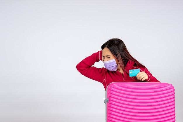 Mulher jovem com bolsa rosa na máscara segurando o cartão do banco na parede branca.
