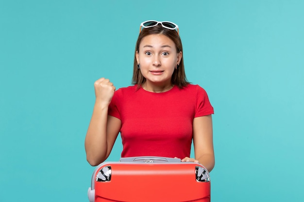 Mulher jovem com bolsa vermelha no espaço azul claro de frente