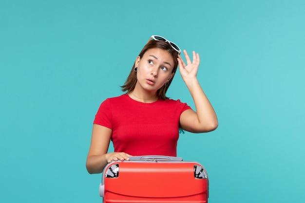 Mulher jovem com bolsa vermelha se preparando para as férias na mesa azul