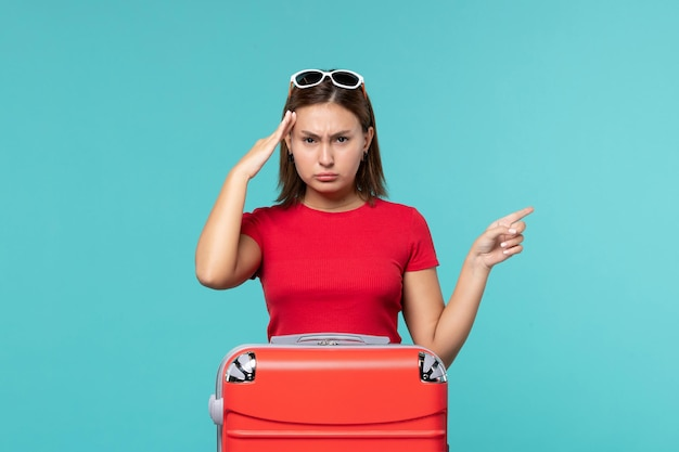 Mulher jovem com bolsa vermelha se preparando para as férias no espaço azul claro de frente