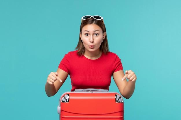 Mulher jovem com bolsa vermelha se preparando para as férias no espaço azul