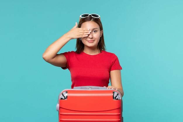 Mulher jovem com bolsa vermelha se preparando para as férias no espaço azul.