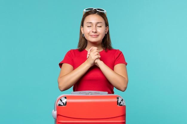 Mulher jovem com bolsa vermelha se preparando para as férias sorrindo no espaço azul.