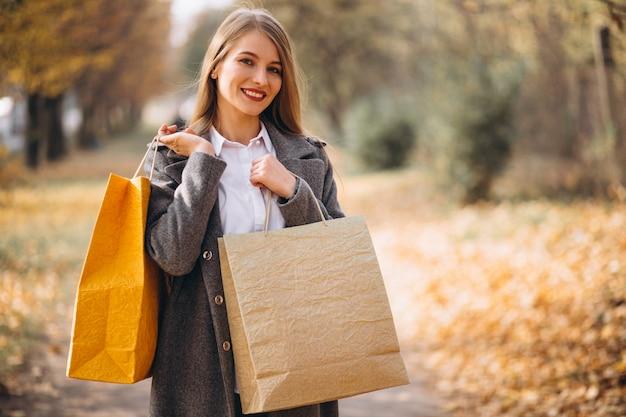 Mulher jovem, com, bolsas para compras, andar, parque