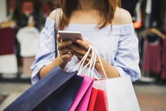 Mulher jovem, com, bolsas para compras, em, a, loja