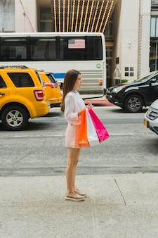 Mulher jovem, com, bolsas para compras, perto, estrada